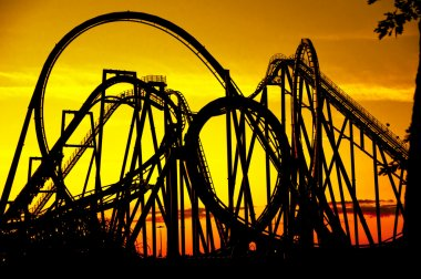 Silhouette of a roller coaster at sunset, after a sunny day at fair isolated on yellow background