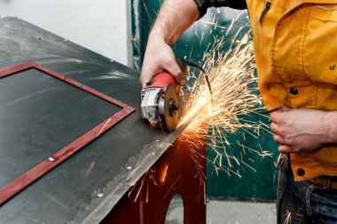industrial worker cutting metal and grinding steel with tools