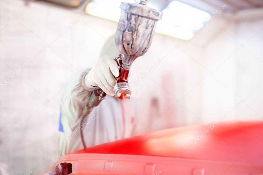 Close-up of spray gun and worker painting a car