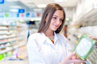 Pharmacist and health care worker in pharmacy with medicine and drugs