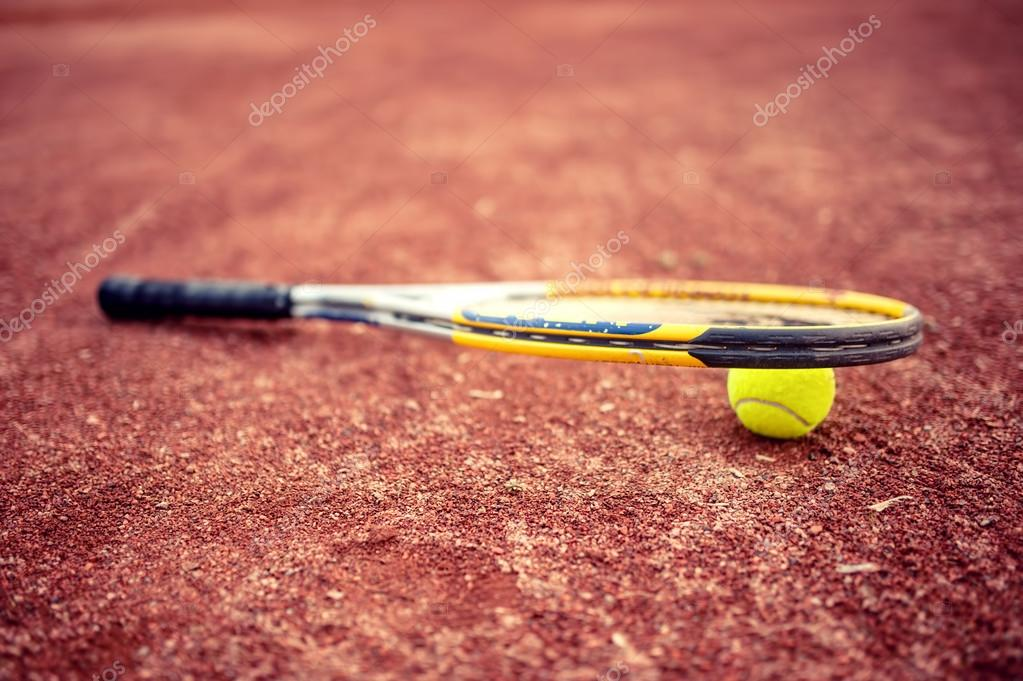 Close-up of tennis racket and ball on clay tennis court