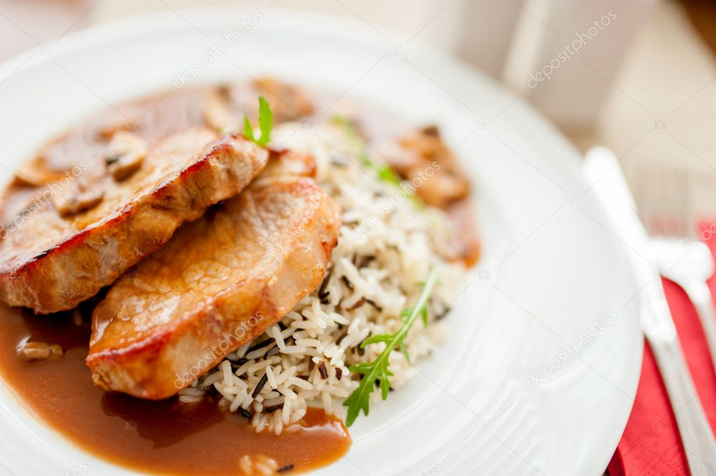 Grilled succulent pork chop and rice as main course, fancy restaurant