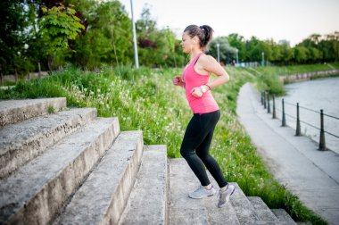 Healthy lifestyle sports woman running on street stairs along river