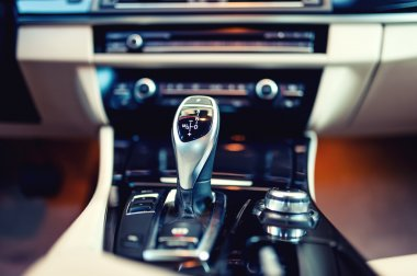 Automatic gear shifter in a new, modern car. Car interior with close-up of automatic transmission and cockpit background. Vintage effect