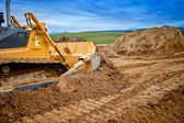 Schwere Planierraupe und Bagger beladen und roter Sand oder Erde auf Straßenbaustelle bewegt