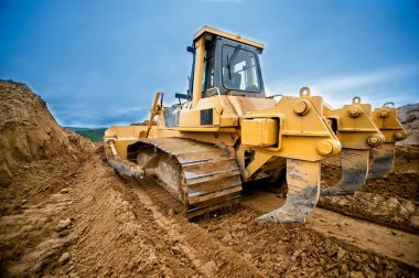 close-up of bulldozer or excavator working with soil on highway