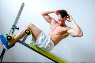 Handsome muscular man doing sit-ups on a incline bench at fitness center or gym