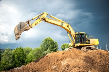 Backhoe and industrial excavator working in construction site, quarry and loading earth in dumper truck