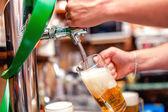 Fényképek sör a pub csapolt söröket csapos részlete. Csapos ömlött egy korsó sör