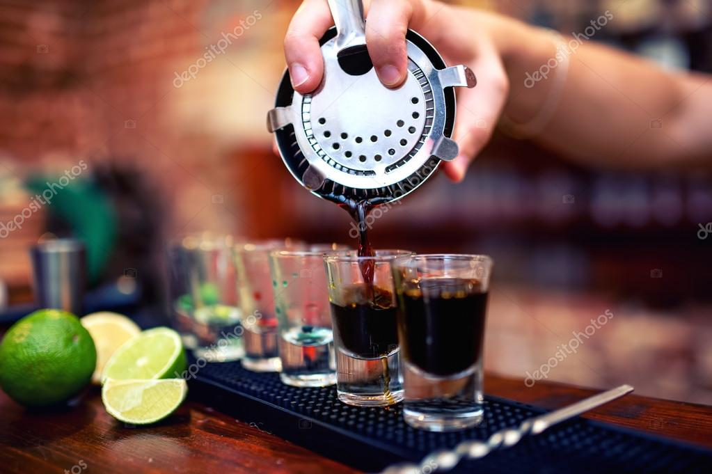 Barman mixing and pouring a summer alcoholic cocktail into small, shot glasses on counter