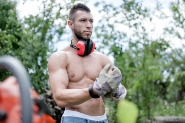 Portrait of male worker, putting on protective gloves and gear and cutting wood with chainsaw