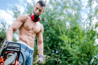 Portrait of aggressive athletic man with chainsaw getting ready for fire wood cutting