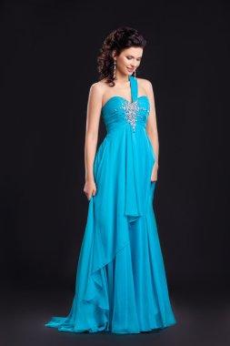 Fashion style. Graceful woman in classic long cyan dress posing