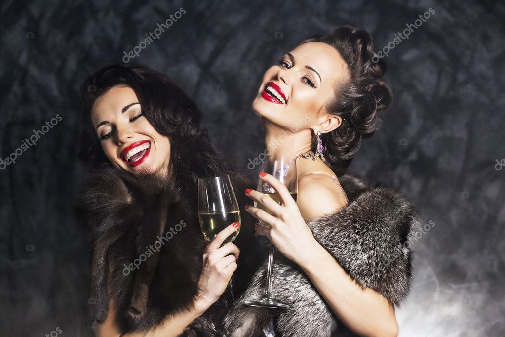 Joy. Elation. Rich woman laughing with crystal of champagne
