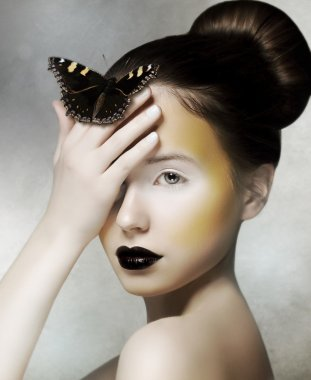Romantic Woman holding Butterfly in her Hand. Fantasy