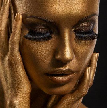 Gilt. Golden Woman's Face Closeup. Futuristic Giled Make-up. Painted Skin