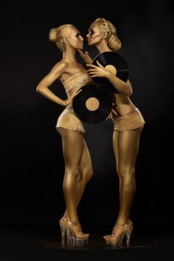 Futurism. Creativity. Glossy Gloden Women with Vinyl Record over Black. Shiny Gilded Bodyart