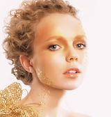 Stylizovaný zlatý ženský obličej. Vlnité vlasy. Professional bronzový make-up