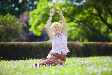Wellness. Mental Health. Optimistic Old Woman Exercising in Open Air