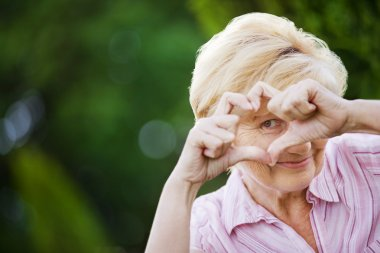 Positivity. Happy Funny Senior Woman Showing Symbol of Heart