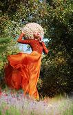 Fotografie extravagante Frau im Kleid und luxuriöse Perücke mit falschen Haare flattern
