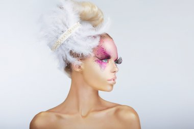 Creativity. Glamorous Fashion Model with Fancy Hair-do with Feathers