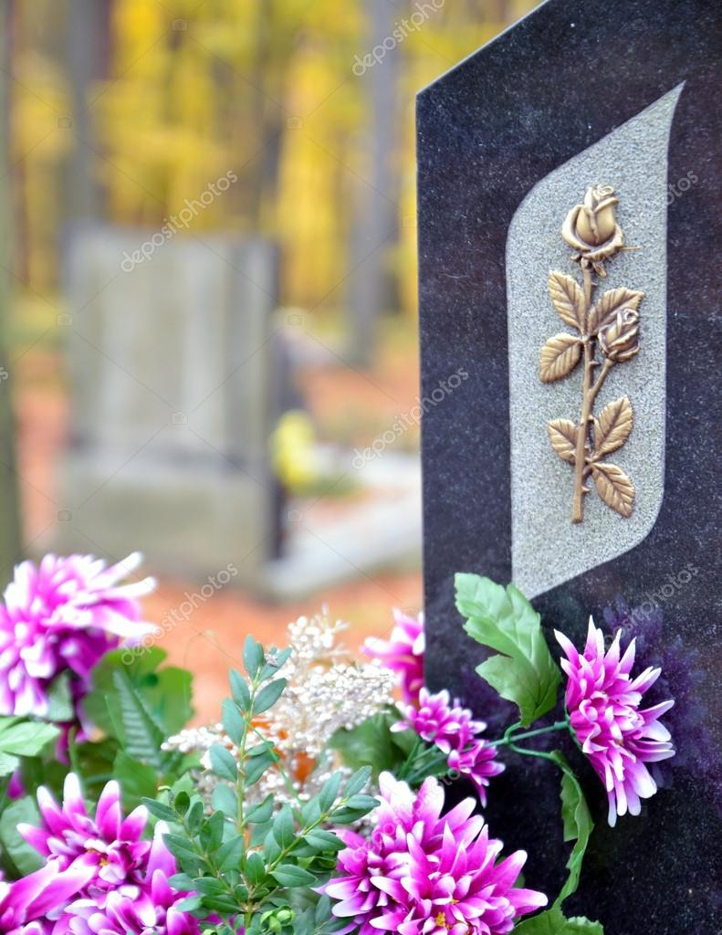 Tombstone with golden rose and purple flowers