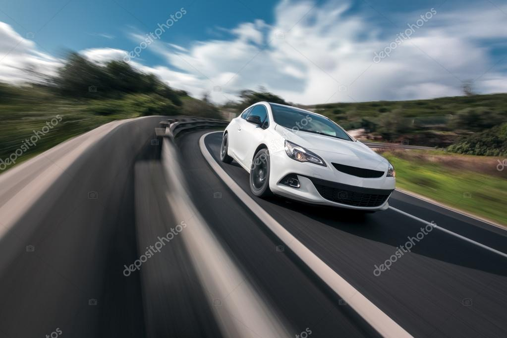 White car cornering in mountain road with speed blur