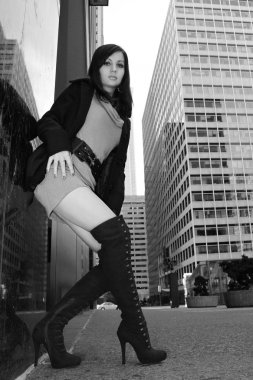 Brunette girl in sexy boots posing in the city, black and white