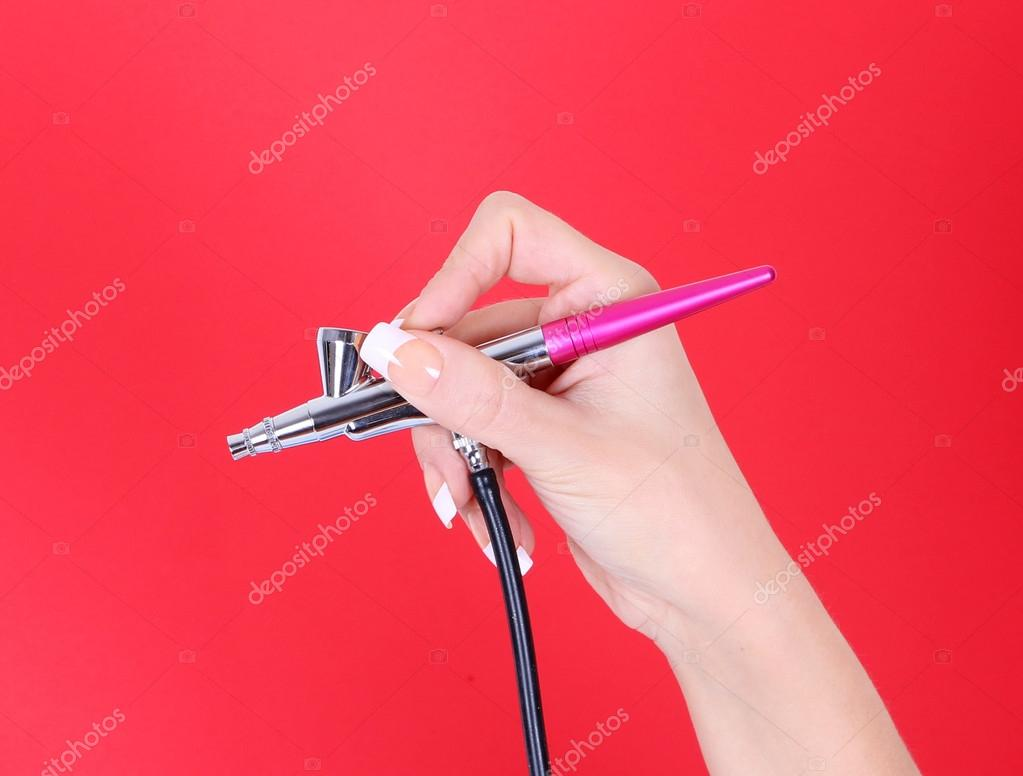 Cosmetic airbrush in hand over red background