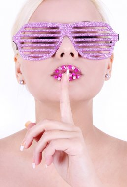 Young woman in glamour pink glasses with finger on her crystal decorated lips, fashion