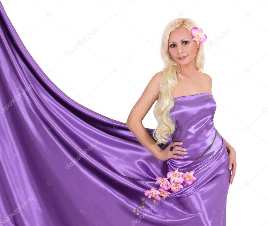 Sexy Blonde Young Woman In Purple Silk Dress With Orchid Flowers