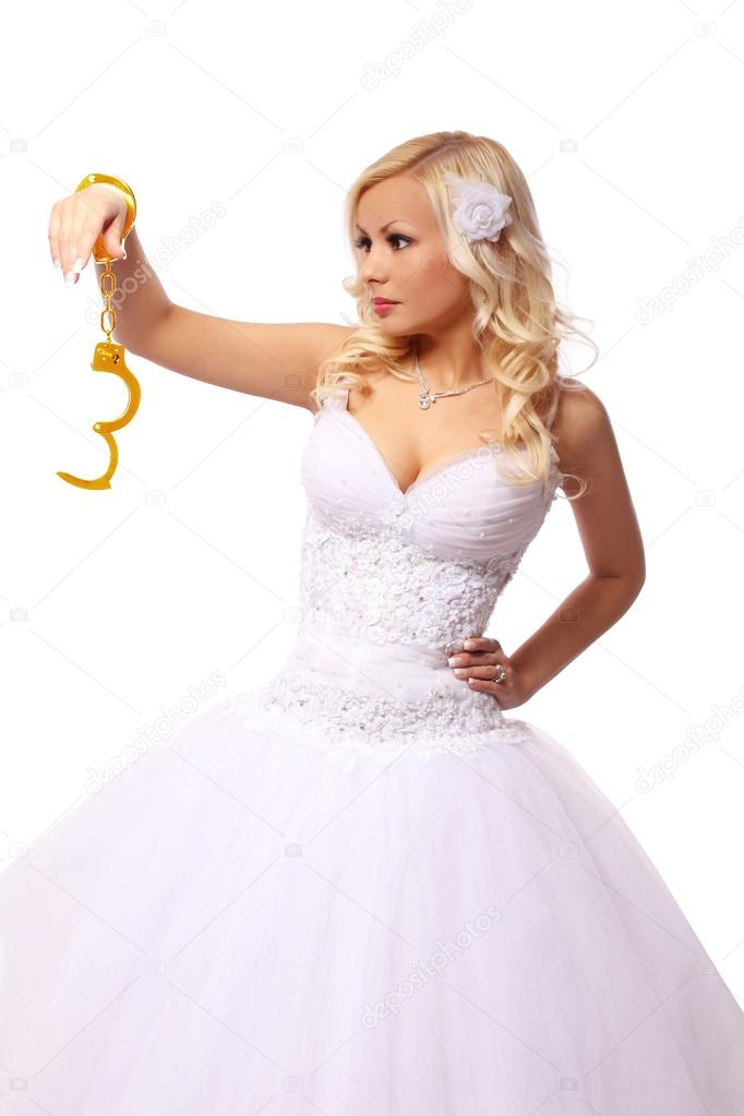 Bride in gold handcuffs. beautiful blonde young woman thinking isolated on white background. concept