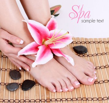 Manicured female bare feet with pink lily flower and spa stones over bamboo mat. Feet care.
