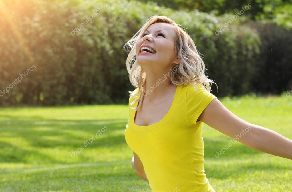 Happy girl enjoying the Nature on green grass. Beautiful blonde young woman smiling with arms outstretched. Outdoor