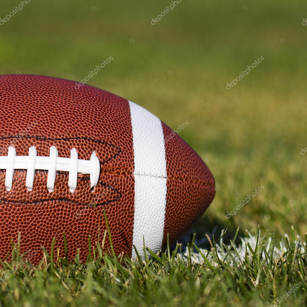 American Football on the field with yard line and green grass. Closeup