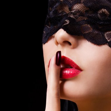Hush. Sexy woman with finger on her red lips showing shush. Erotik girl with lace mask over black background.