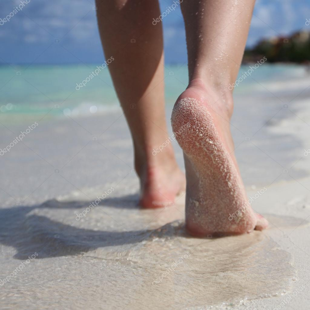 Female Feet on Tropical Sand Beach. Legs Walking. Closeup