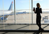 Girl Waiting her Flight in Airport Terminal. Silhouette of Young