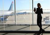 Mädchen warten ihren Flug im Flughafen-terminal. Silhouette der Junge