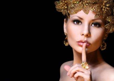 Fashion Girl with Gold Jewelries over black background. Beauty y
