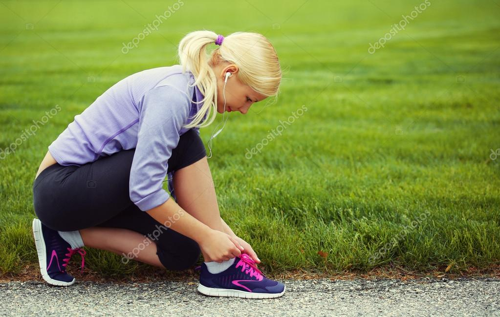 Woman runner tying running shoes. Blonde Girl over Green Grass
