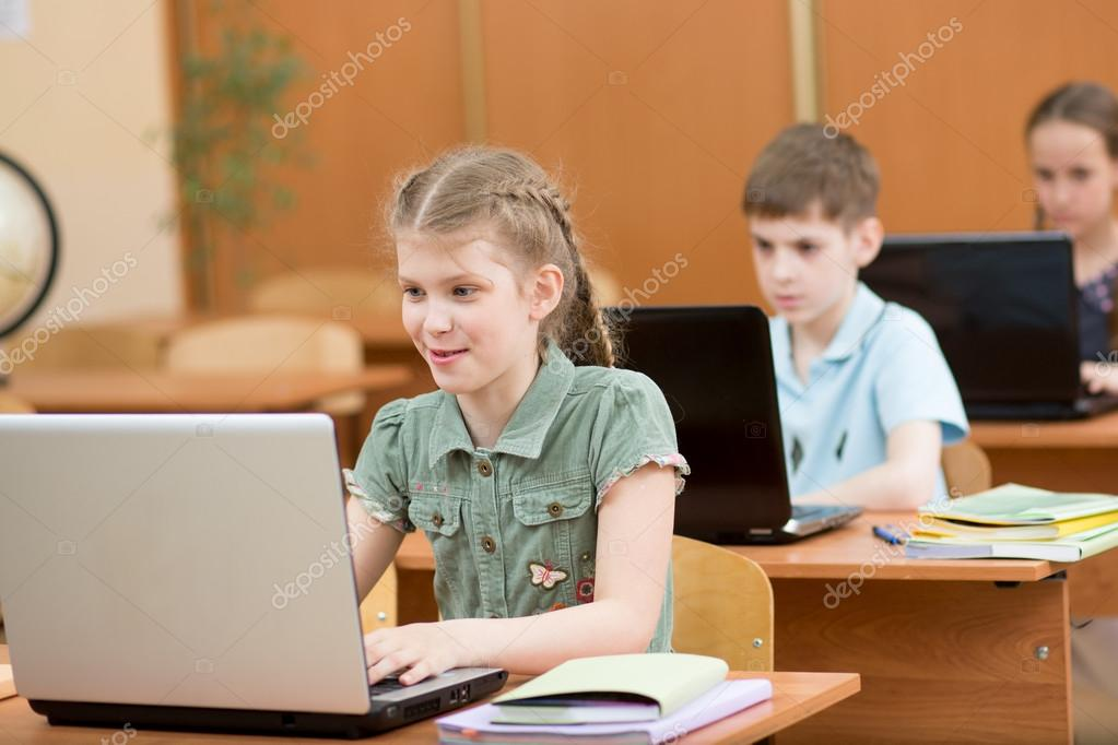 school kids using laptop at lesson