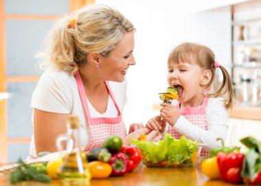 Mother feeding kid daughter vegetables in kitchen