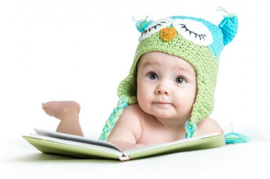baby in funny knitted hat owl with book on white background