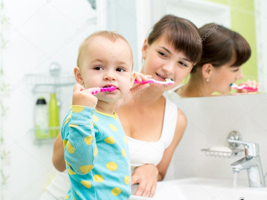 Cute Little Girl With Her Mother Brushing Teeth Near