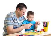 Šťastný otec a dítě chlapec spolu hrají jíl
