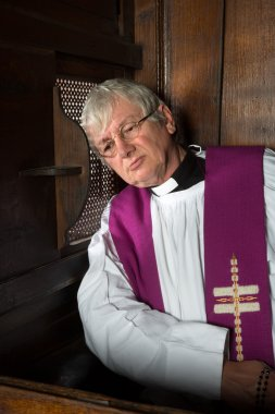 Vicar in confession booth