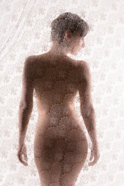 Naked woman behind lace curtain