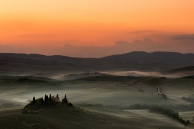 Early dawn in the Tuscan hills of San Quirico d'Orcia with Belvedere villa still in darkness stock vector